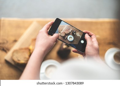 High angle above top view and cropped photo of woman making photo of her breakfast coffee and sandwich on portable telephone equipment. She standing inside loft interior space in restaurant