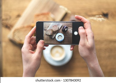 High angle above top view and cropped photo of woman with portable telephone equipment in hands. She making photo for social network standing inside loft interior space in restaurant
