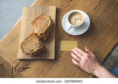High angle above top view photo of wooden table with cup of beverage, sandwich and lady hand holding plastic credit card