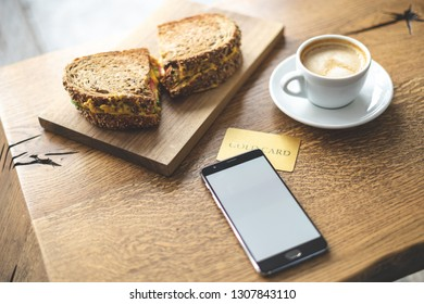 High angle above top view close up photo of portable telephone equipment, snack and beverage on wooden table inside loft interior space in restaurant