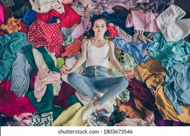 High angle above view photo of pretty focused lady stay home quarantine spring cleaning household lying many clothes heap stack floor prepared untidy dirty stuff resting meditating indoors