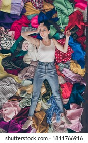 High angle above view photo of stressed tired lady stay home quarantine general spring cleaning household lying many clothes heap stack floor pick select look outfit nothing to wear indoors