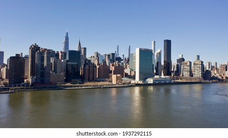 A high angle, aerial view of Manhattan from over the East River in New York. It was taken on a sunny day with clear blue skies.