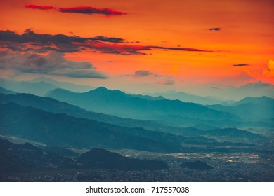 High angle aerial view over Pokhara City, Nepal at evening. Blue mountain misty range and orange sunset cloudy sky in the background. Nature landscape. Travel, holidays, recreation concept