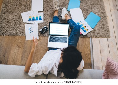 High angle anonymous female sitting on floor with opened netbook on laps amidst papers and working on project at home