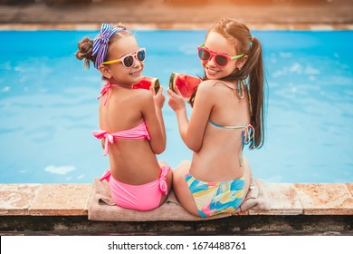 High angle back view of happy friends in sunglasses and colorful swimsuits with slices of fresh tasty watermelon looking, over shoulder at camera and smiling while sitting on poolside pool