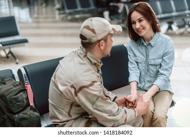 High angle of beautiful woman wearing casual and situating opposite her husband in military uniform. They are holding hands while smiling to each other indoors. Homecoming concept
