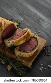 High angle beef wellington cooking or boeuf en crout cut into slices on a chopping board black background.