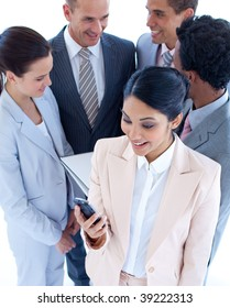 High angle of businesswoman sending a text with a mobile phone and her team in the background