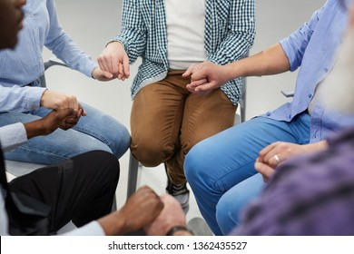 High angle close up of people holding hands sitting in circle during therapy session in support group, copy space