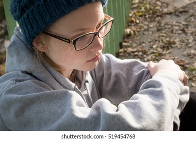 High angle, close shot of girl with glasses sitting in urban exterior autumn setting, looking lonely, sad, thoughtful