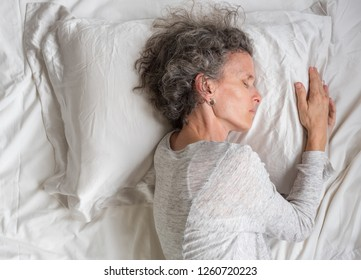 High angle close up side view of middle aged woman with grey hair sleeping on silk pillow case in messy bed (selective focus)