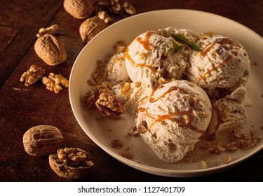 High Angle Close Up Still Life of Scoops of Maple Walnut Ice Cream Drizzled with Caramel Sauce and Garnished with Walnuts in Large Bowl on Wooden Table