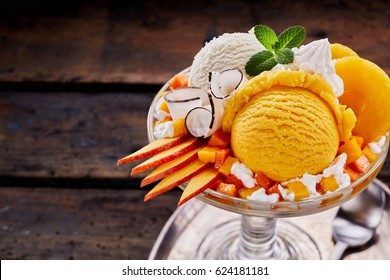 High Angle Close Up View of Sundae Made with Scoops of Vanilla and Peach Flavored Ice Cream, Slices of Fresh Fruit, Whipped Cream and Mint Garnish Served in Glass Dish on Wood Table with Copy Space