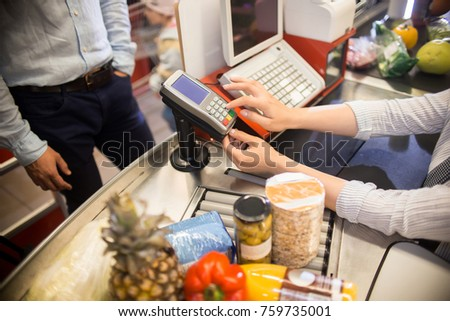 High angle closeup of cashier entering price to paying terminal at cash desk in supermarket