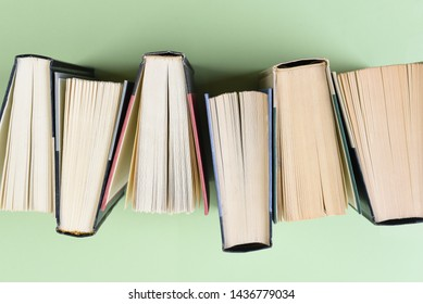 High angle closeup of a row of books on a light green background.