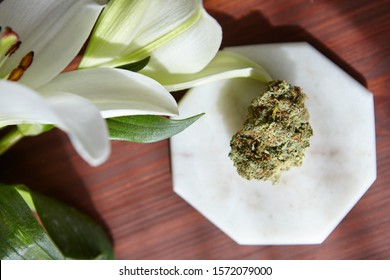 A high angle closeup shot of a piece of dry cannabis on a white plate under beautiful lilies