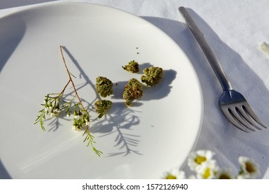 A high angle closeup shot of pieces of dry cannabis on a white plate