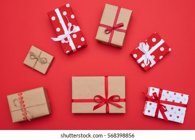 High angle of the composition of present boxes place in order by size. The biggest classic gift box wrapped in a brown vintage paper situated in the center