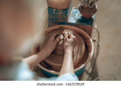 High angle of craftswoman arms working on pottery wheel while situating in potter's studio. She is sculping from clay pot. Concept of ceramic art