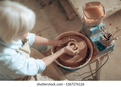 High angle of craftswoman working on pottery wheel while situating in potter's studio. She is modelling decorative object. Concept of ceramic art