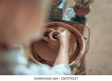 High angle of craftswoman's arms working with wet clay on pottery wheel while situating in potter's studio. She is modelling decorative object. Concept of ceramic art