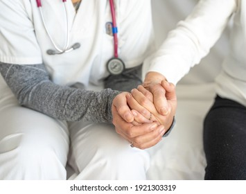 High angle of crop anonymous medic holding hand of senior female while sitting together on couch