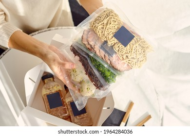 High angle crop anonymous person showing Ramen soup ingredients packed in vacuum sealed bags above lunch box