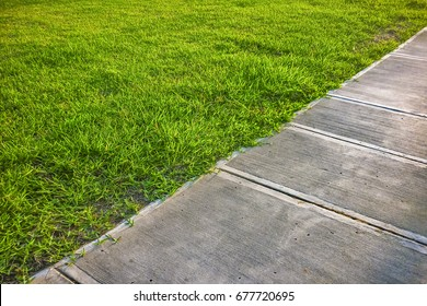 High angle detail shot of empty sidewalk surrounded by grass