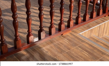 High angle and diagonal view of vintage glossy wood banister on wooden tile floor with stairway