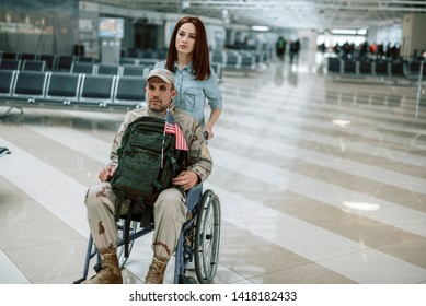 High angle of disabled Caucasian soldier sitting in wheelchair with backpack on knees. Young couple is calm and serious. Homecoming and military concept