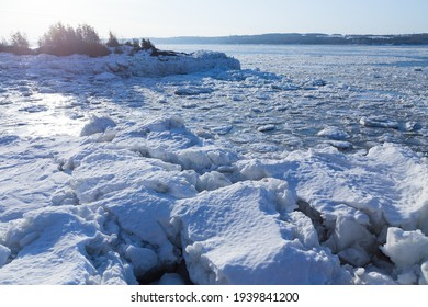 High angle east view of an icy cove in the St. Lawrence River seen in Ste. Petronille, Island of Orleans, with the south shore in the distance, Quebec, Canada