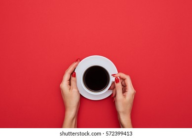 High angle of female hands hold a cup of strong coffee on red desktop and with copy space