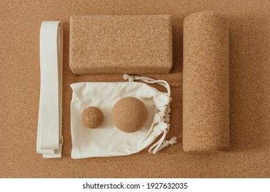 High angle flat lay of props for yoga and self care techniques: myofascial release, yoga therapy, set on a cork mat background. Belt, cork massage balls, cork roller and block.