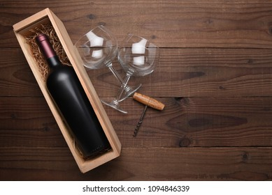 High angle flat lay still life of a wine bottle in a wood box with two wine glasses and corkscrew. Horizontal format on rustic wood table with copy space.