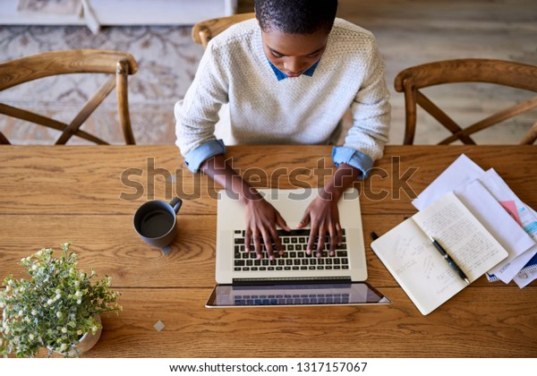 High angle of a focused young African American female entrepreneur working online with a laptop while sitting at a table at home