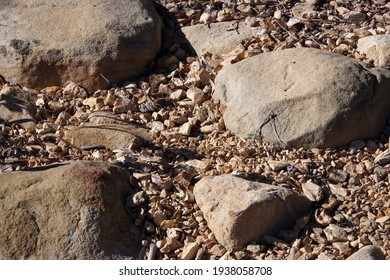 High angle full frame close-up view of a dry desert ground with rocks and stones and gravel