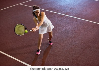 High angle full length  portrait of forceful woman playing tennis in indoor court, copy space