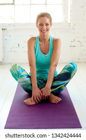 High angle full length shot of happy middle aged woman sitting in crossed legged pose while relaxing after yoga exercises.
