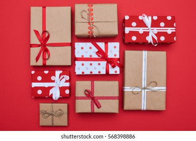 High angle of the group of festive wrapped gift boxes isolated over flat lay red background. Cute presents tied with ribbons and rope