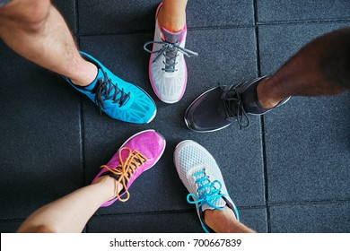 High angle of a group of people's feet wearing running shoes standing together in a huddle on a gym floor