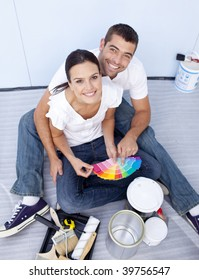 High angle of happy couple choosing colours to paint new house