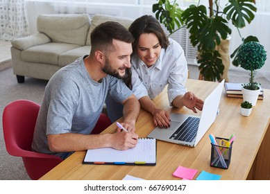 High angle of husband writing in notebook while wife showing something to him in laptop