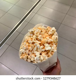 High angle image of hand holding popcorn with chutney flavouring
