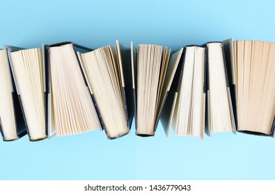 High angle image of a row of books standing on end on a light blue background.