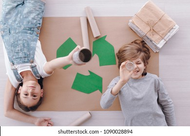 High angle of kids lying on paper during environmental protection classes at school
