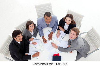High angle of multi-ethnic business people smiling at the camera in a meeting