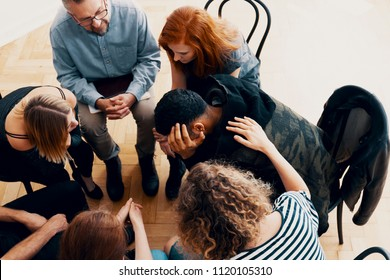 High angle on crying spanish man sitting with his support group and therapist in a circle during therapy
