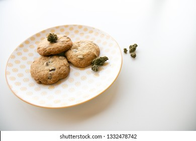 High Angle on a Yellow Patterned Plate with Chocolate Chip Cookies and Marijuana Buds