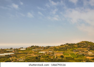 High angle panoramic view of the Riviera of Flowers with the typical glasshouses for the floriculture and the Ligurian Sea in the background in a sunny summer day